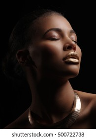 Fashion studio portrait of an extraordinary beautiful nude african american model with perfect smooth glowing mulatto skin, make up, full golden lips, shaved haircut and gold necklace, profile
