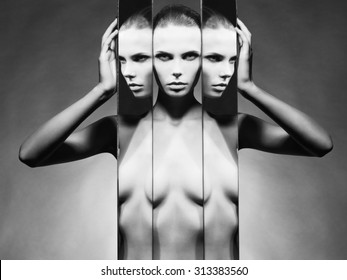 Fashion studio portrait of nude elegant woman and mirrors on black background