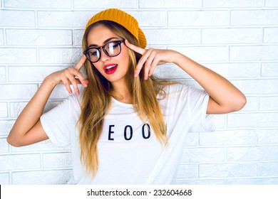 Fashion studio portrait of pretty young hipster blonde woman with bright sexy make up and glasses , wearing stylish urban t shirt and hat, White urban wall background.