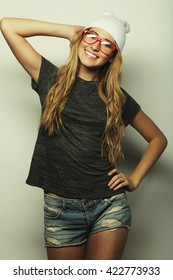 Fashion studio portrait of pretty young hipster blonde woman with glasses , wearing stylish urban t shirt and hat, over white background