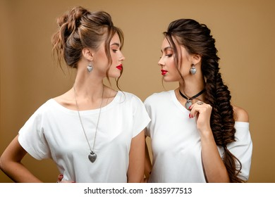 Fashion studio portrait of two beautiful women with silver necklace.