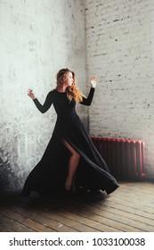 Fashion studio portrait of woman in long black dress