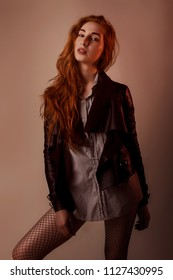 Fashion studio portrait of woman with red long hair in shirts and leather jacket and black fishnet tights, warm tones, fashion and style concept