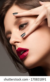 Fashion studio portrait of young beautiful woman with bright makeup and black manicure