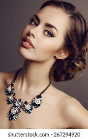 fashion studio portrait of young beautiful girl with dark hair and evening makeup with luxurious necklace