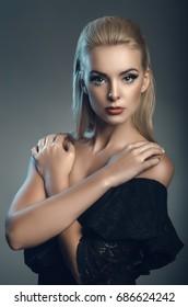 fashion studio portrait of young beautiful woman on dark background, blue backlight