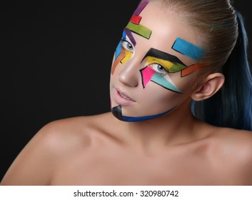 fashion studio portrait of young girl with bright geometric pattern on her face.Halloween style