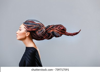 Fashion studio shoot of a mixed race woman with a creative colorful hairstyle in the form of a pigtail braided from dreadlocks in the technique of zizi. The concept of hairdressing art