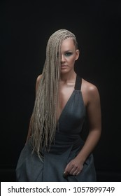 Fashion studio shoot woman with a creative hairstyle in the form of a pigtail braided from dreadlocks in the technique of zizi. The concept of hairdressing art