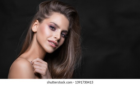 Fashion studio shot of beautiful smiley young woman with make-up. Close-up portrait. Beauty service and skin care concept