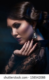 Fashion studio shot of  beautiful young woman with retro hairstyle and elegant earrings
