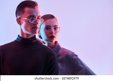 Fashion studio shot. Handsome young man and beautiful young woman posing together in stylish glasses. Optics. Business style.