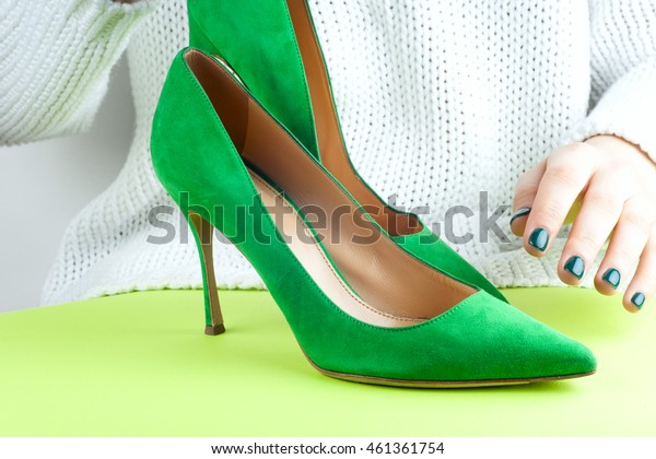 Fashion studio shot of shopping girl holding a high heel shoe in her hand. Isolated on white background.