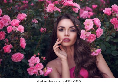 Fashion style beauty romantic portrait of young pretty beautiful woman with long curly hair posing between pink roses. Stunning girl looking at you or in camera