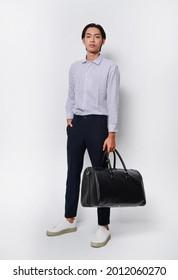 Mode und Stil. Ganzer junger Mann mit Streifen, Hemd mit Hose, die eine schwarze Handtasche im Studio hält