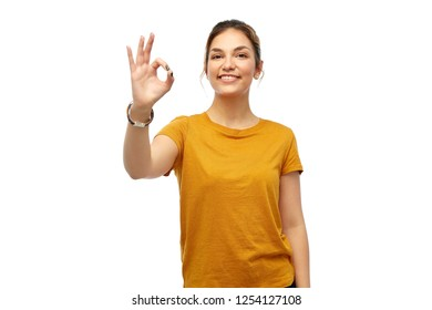 fashion, style and gesture concept - happy smiling young woman or teenage girl over white background showing ok hand sign