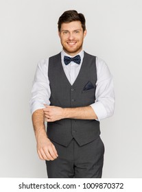 fashion, style and holidays concept - happy man in festive suit dressing for party and adjusting bowtie