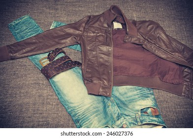 Fashion style: leather jacket, blue jeans, a leather belt with a buckle. Youth urban clothing. Vintage style