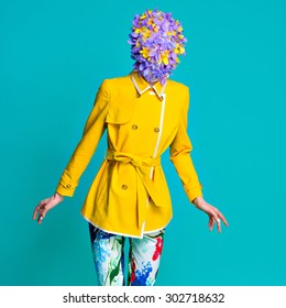 Fashion style model in yellow coat and art flowers accessories on head posing in studio on blue background