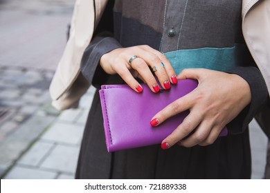 Fashion and style, money and savings. Woman with a bright red manicure and silver rings holds a large purple leather purse in her hands. Woman's hands with wallet