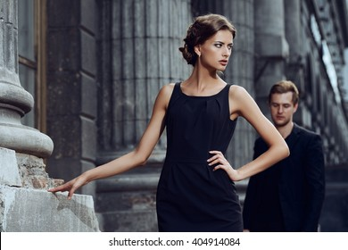 Fashion style photo of a beautiful couple over city background.