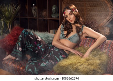 Fashion style photo of beautiful young woman in boho style clothes. Girl wearing flower hairband. Trendy curly hairstyle and glamour natural makeup.