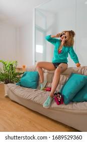Fashion style portrait of a beautiful woman on a sofa talking phone