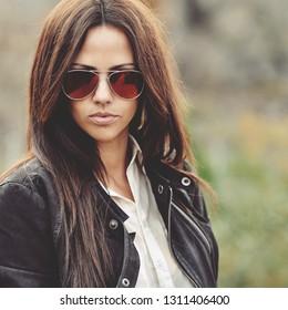 Fashion style portrait of confident woman in sunglasses