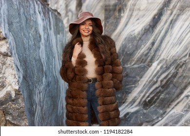 Fashion style portrait of young beautiful glamorous woman in brown fur coat and leather hat standing and posing between gray marble walls at quarry. Photo with natural lightning