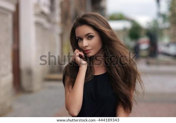 Mode-stijl portret van jonge mooie elegante vrouw in zwarte jurk wandelen in de straten van de stad op een winderige saaie dag.