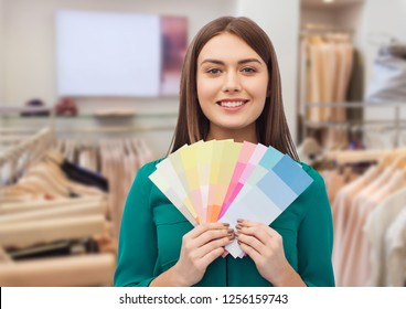 fashion, style and shopping concept - smiling young woman with color swatches or samples over clothing store background