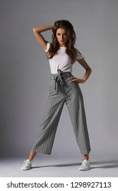 Fashion style studio portrait of beautiful young woman. Gray wide leg pants and white t-shirt. Model standing and posing against gray background