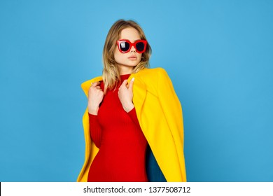 fashion style woman in a bright yellow jacket with glasses on a blue background