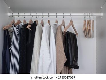 Fashion stylist clothes basic wardrobe.Neutral colors: white, black, beige. White closet, wooden hanger shoulders.