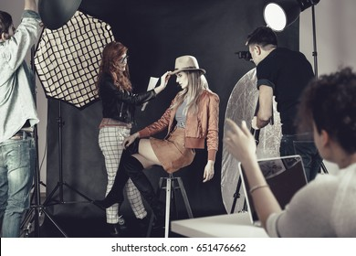 Fashion stylist with professional model at photoshoot backstage