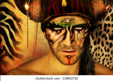 Fashion stylized concept portrait of a young man with tribal face painting and animal elements in front of a animal print background