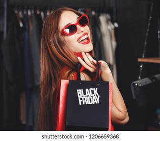 Fashion successful young woman wearing sunglasses and red dresses posing with black friday bag in fashion mall during shopping process, concept of consumerism, Black Friday, sale, rich life