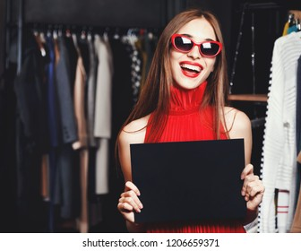 Fashion successful young woman wearing sunglasses and red dresses showing black card in fashion mall during shopping process, concept of consumerism, Black Friday, sale, rich life