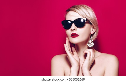 Fashion summer Beautiful Young girl face in glamour sun glasses studio portrait on pink or red background