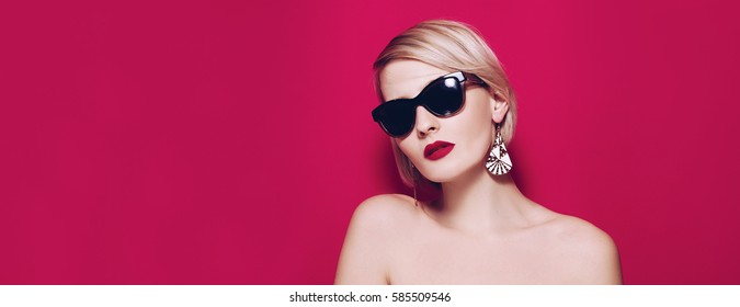 Fashion summer Beautiful Young girl face portrait banner in glamour sun glasses studio portrait on pink or red background.