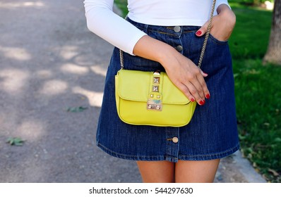 Fashion summer girl with little accessories bag. Trendy outfit jeans skirt