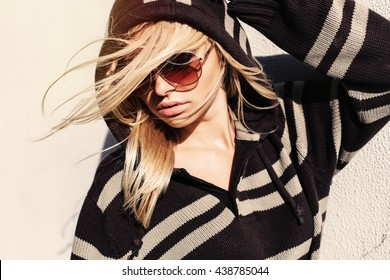 Fashion summer outdoor portrait of young blonde girl posing on the street on light warm wall background in sunglasses