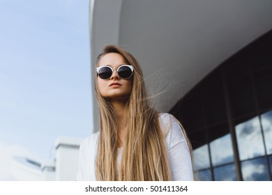 Fashion summer outdoor portrait of young blonde girl posing on the street on light warm wall background in sunglasses.Beautiful and young girl in a coat walking around the city in the summer.