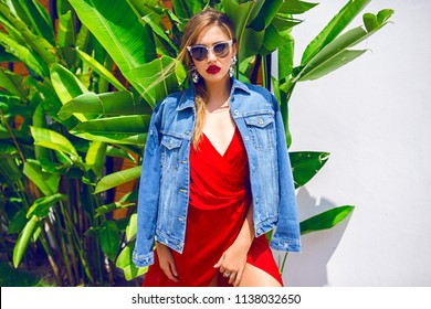 Fashion summer portrait of stunning woman posing near palm trees, wearing sexy red long dress, luxury accessories and sunglasses, vacation mode style.