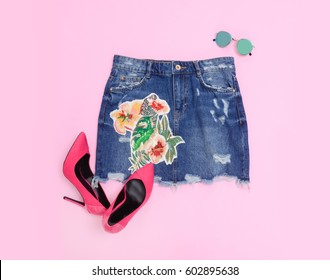 Fashion. Summer woman accessories-embroidery floral jeans skirt ,sunglasses, shoes-pink background