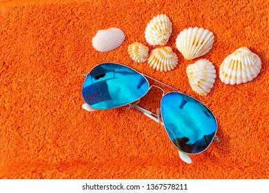 Fashion sunglases near seashells on orange beach towel. Conceptual photography suggesting the summer holiday and time for relaxing and charging batteries.