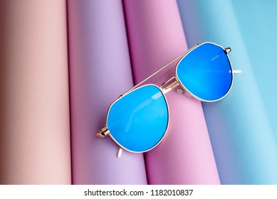Fashion of Sunglasses with blue lens put on colorful paper background