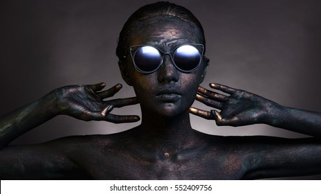 Fashion Sunglasses on dark Bronze stone rough skin body paint artwork, studio lighting with color shade background