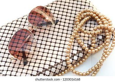 Fashion sunglasses on metallic gold evening bag and pearl necklace woman accessory fashion set on white background