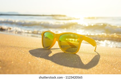 Fashion sunglasses on sea beach with clear blue sky. Summer holiday relax background